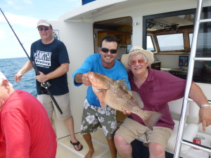 "Left to Right: Gary Smith, Captain Steve Skevington and Dennis Macalister holding a 25-inch Red Grouper caught in ""Paradise."""